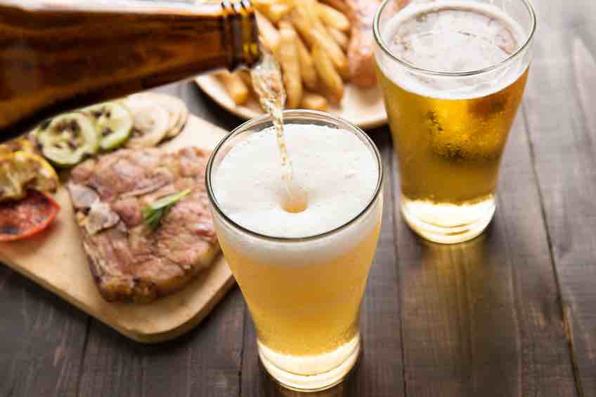 Beer being poured into glass with gourmet steak and french fries on wooden background