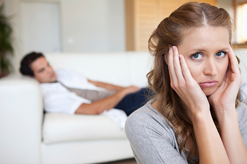 Woman suffering from headache with man on the sofa